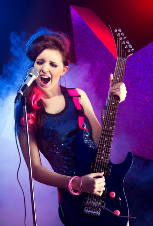 Young teenager rock star singing and playing electric guitar on stage. photo