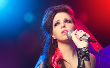 talent show: Young pop star girl singing on stage close up. Stock Photo