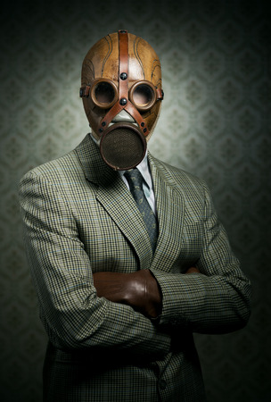 Vintage businessman wearing a gas mask with retro wallpaper on background. photo