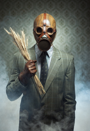 Man wearing a gas mask and holding ears of wheat with toxic smoke on background. Stock Photo