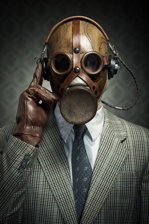 Man wearing vintage gas mask and headphones listening to music. Stock Photo