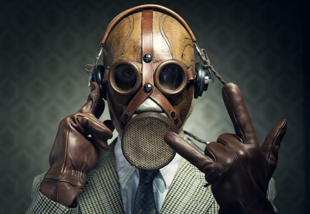 Man wearing gas mask and headphones making rock sign. Stock Photo