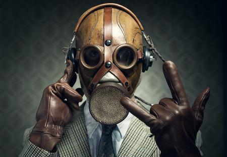 Man wearing gas mask and headphones making rock sign. photo