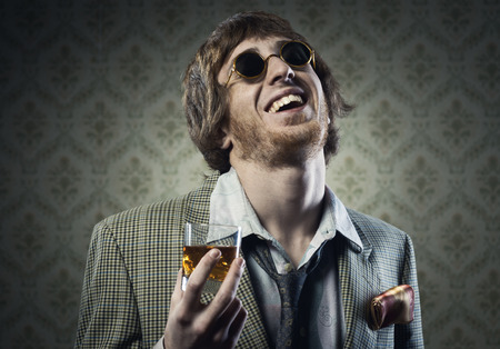 Funny guy holding a glass of whisky and posing against vintage wallpaper. photo