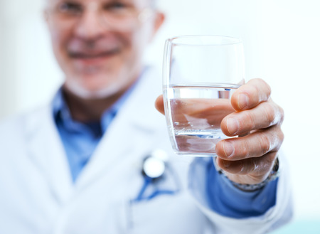 dietology: Doctor offering a glass of water, healthy lifestyle concept.