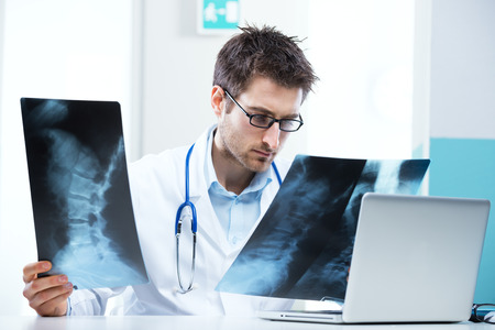 Professional radiologist examining an X-ray image of human spine. photo