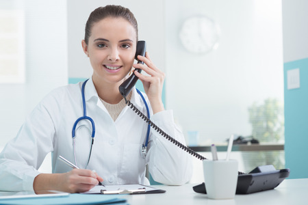 answering: Young female doctor sitting at her desk and talking on the phone