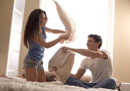Portrait of happy loving couple having a pillow fight in bed photo
