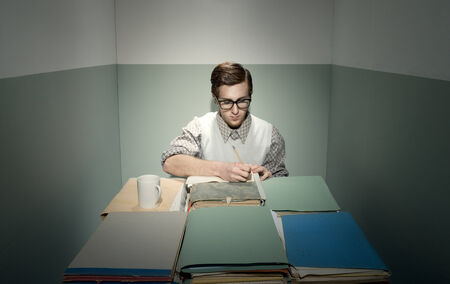 desk tidy: Nerd young man at desk in his small sad room. Stock Photo