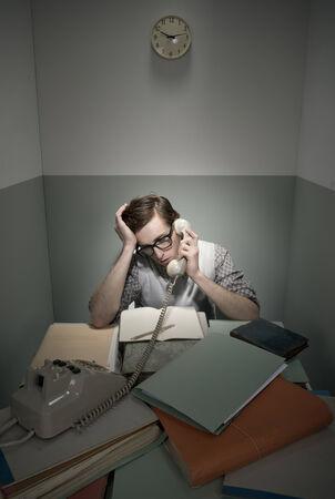 oficina desordenada: Friki retro en el teléfono con escritorio desordenado en una habitación pequeña.
