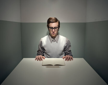eccentric: Geek funny guy with notebook in a small gray room.