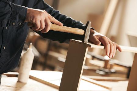 carpintero: Carpintero que martilla un mueble para el montaje.