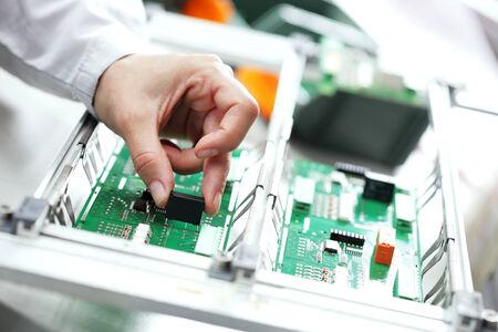 Technicien assemblage de composants electonic à sa table de travail.