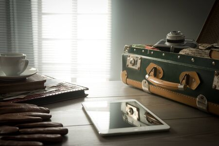 Travelers suitcase with vintage items, tablet and a cup of coffee. photo