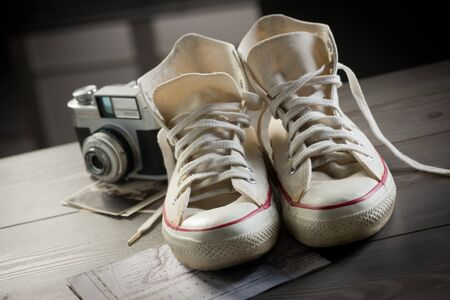 Canvas shoes with vintage camera and world map, youth adventure trip concept. photo