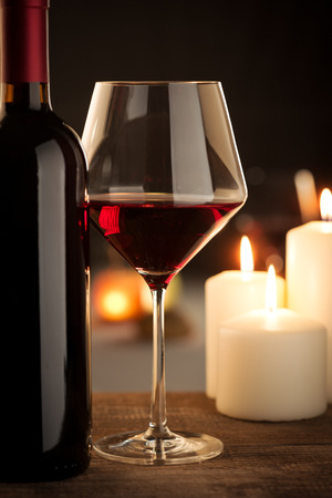 merlot: Red wine glass and bottle close up with restaurant on background. Stock Photo