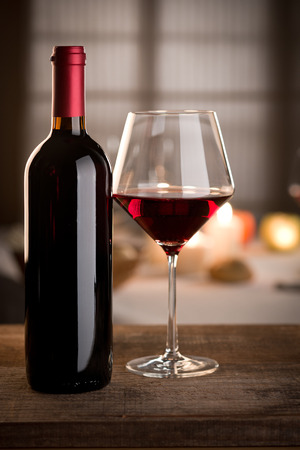 Red wine glass and bottle close up with restaurant on background. Stock Photo