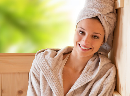 Young attractive woman smiling and relaxing in sauna at spa. photo