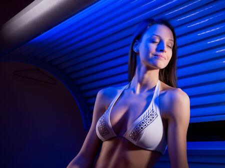 Attraktive Frau trägt Bikini und sitzen auf Sonnenbank.