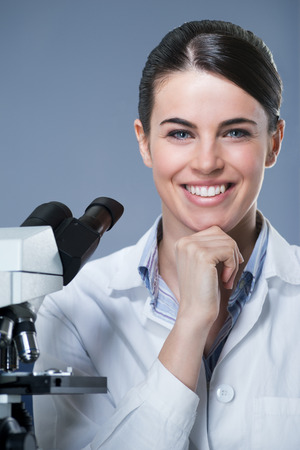 lab technician: Attractive female researcher smiling with hand on chin. Stock Photo
