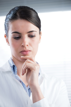 Attractive female researcher thinking with hand on chin. photo