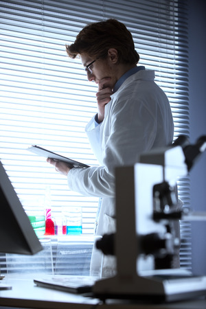 pathologist: Researcher reading medical records in the chemical laboratory with microscope on foreground.