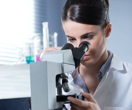 Young female researcher using microscope in the chemistry lab with laboratory glassware on background. photo