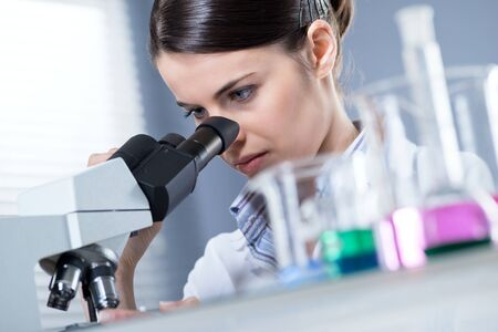Young female researcher using microscope in the chemistry lab with laboratory glassware on foreground. photo