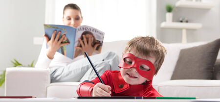 playtime: Cute super hero boy drawing with mother reading on background. Stock Photo