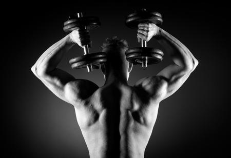 Muscular attractive man weightlifting on dark background.