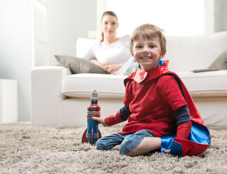 Cute superhero boy paying with toy rocket in the living room with his mother on background. photo