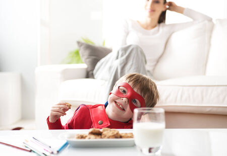 Superhero boy having an healthy snack with cookies and milk with his mother on background. photo