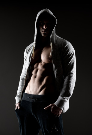 Confident body builder in hooded shirt with bare chest. photo