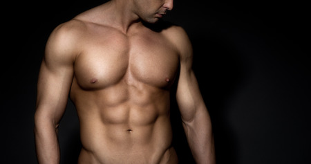 Bare chested muscular man looking down on dark background. photo