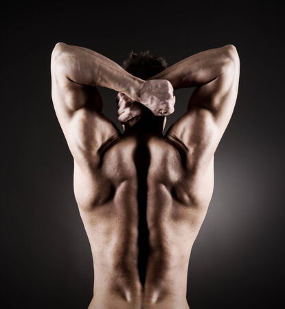 Body builder posing on dark background, rear view. photo