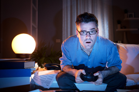 handheld: Man playing videogames late at night in a messy living room, sitting on sofa.