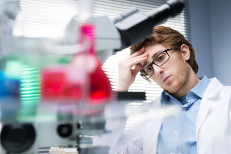 pathologist: Young researcher at work with laboratory glassware on foreground.