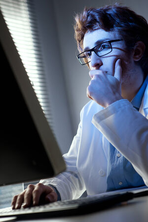 Researcher working at computer in the laboratory with hand on chin. photo