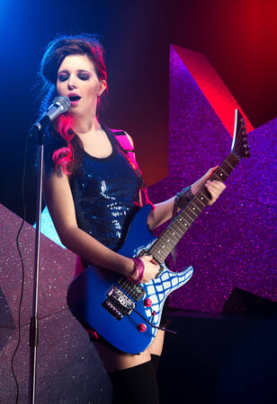 Young teenage rockstar singing and playing electric guitar on stage  photo