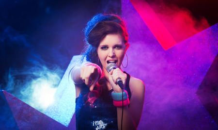talent show: Young beautiful girl singing on stage with star on background  Stock Photo