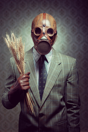 Man wearing a gas mask and holding ears of wheat. photo