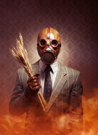 Man wearing a gas mask and holding ears of wheat with toxic smoke on background. photo