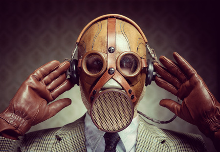 Man wearing vintage gas mask and headphones listening to music. photo