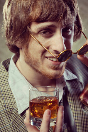 Funny guy holding a glass of whisky and posing  photo