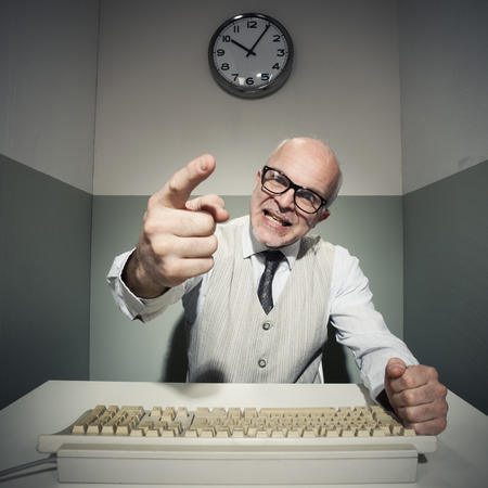 old man on a physical pressure: Vintage office worker pointing and yelling at computer.