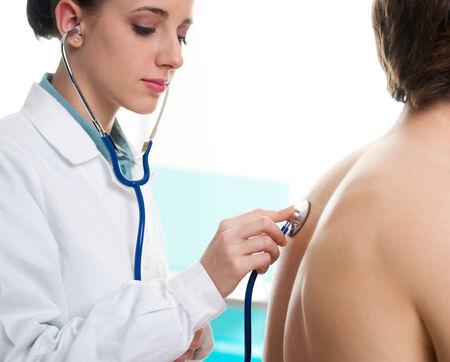 listening back: Female doctor listening mans back through stethoscope  Stock Photo