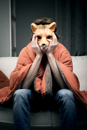 embarassment: Young depressed man wearing a fox mask covered with a blanket.