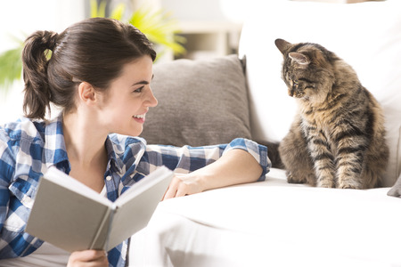 couches: Smiling woman playing with her cat and holding a book in the living room.