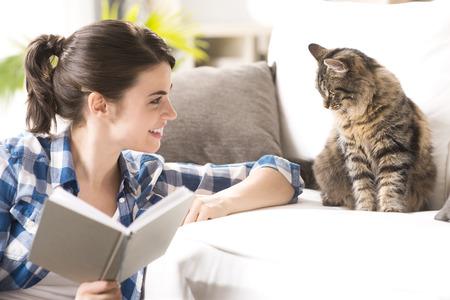 Usmívající se žena hraje s ní kočka a drží knihu v obývacím pokoji.