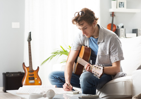 Young man playing guitar and composing a song sitting on sofa.